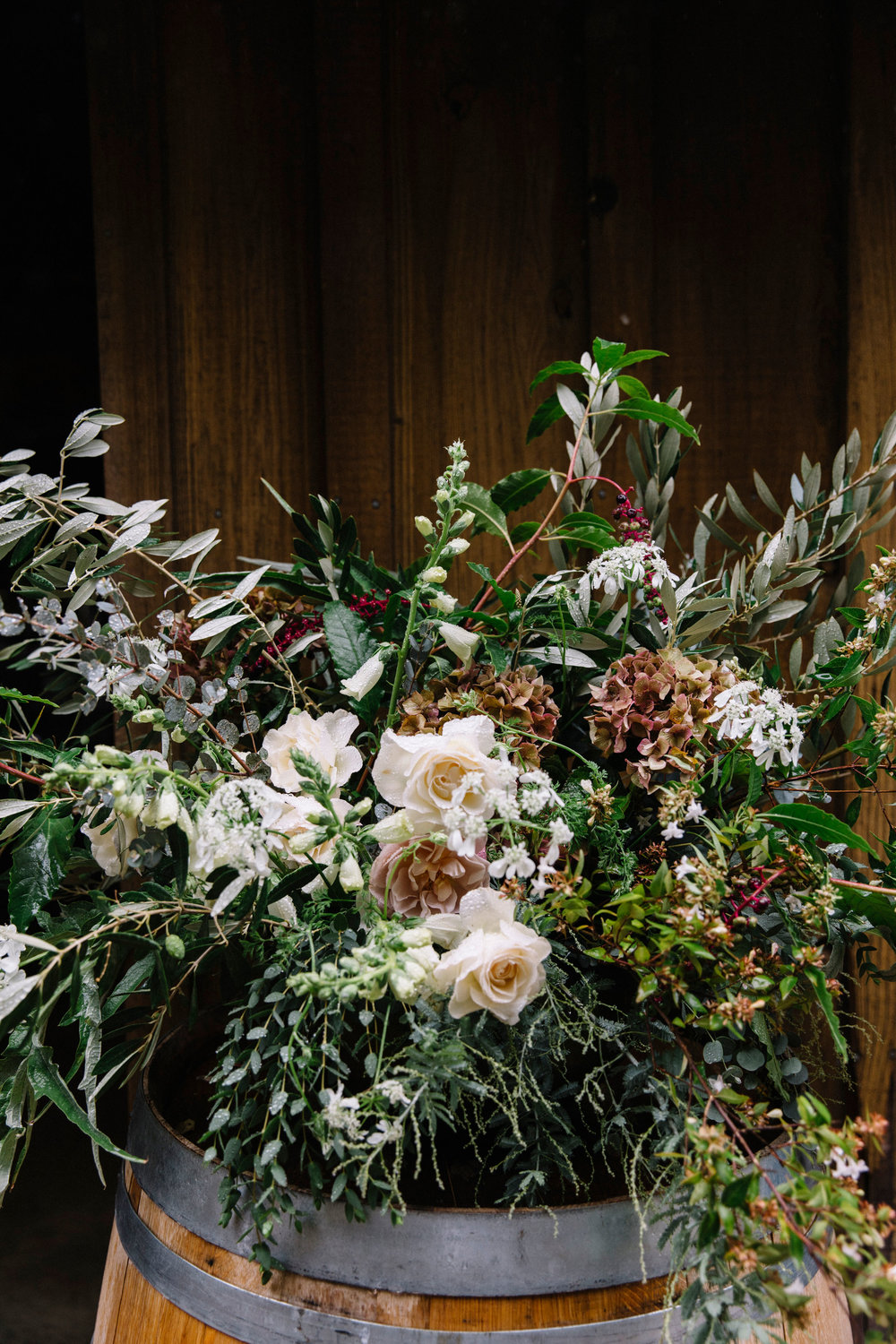 Wedding ceremony flowers in moody hues with light additions by Venn Floral at Ru's Farm in Healdsburg photographed by Lucille Lawrence