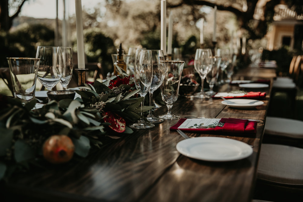 Green garlands, pomegranates, berries, and brass candlesticks for a dramatic wedding tablescape by Venn Floral with Whitney Nelson Events at Beltane Ranch. Photographed by Vera Frances