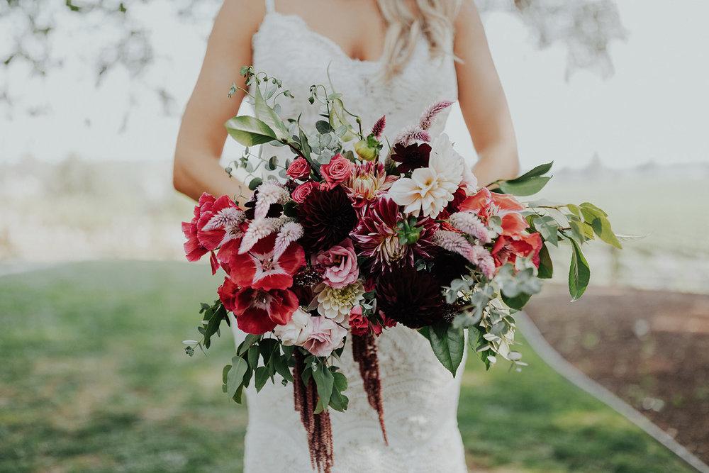 Cascading bridal bouquet in rich vibrant shades by Venn Floral for a stylish Summer wedding at Ru's Farm in Healdsburg photographed by Logan Cole.