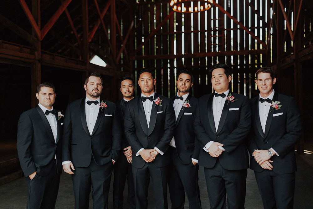 Groomsmen in tuxedos with bright and colorful boutonnieres by Venn Floral in Healdsburg at Ru's Farm photographed by Logan Cole.