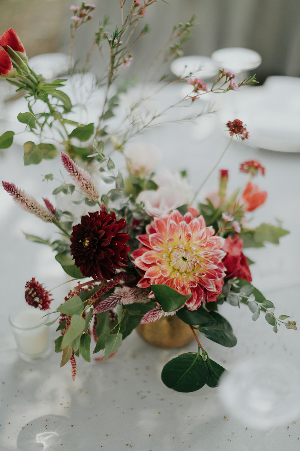 Bright summertime centerpieces with dahlias, scabiosa, godetia and eucalyptus in hammered brass vases by Venn Floral at Ru's Farm in Healdsburg photographed by Logan Cole.