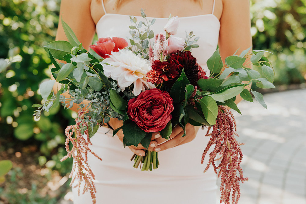 Hot pink, burgundy, magenta, and coral bridesmaid bouquet by Venn Floral photographed by Logan Cole in Healdsburg, California at Ru's Farm.