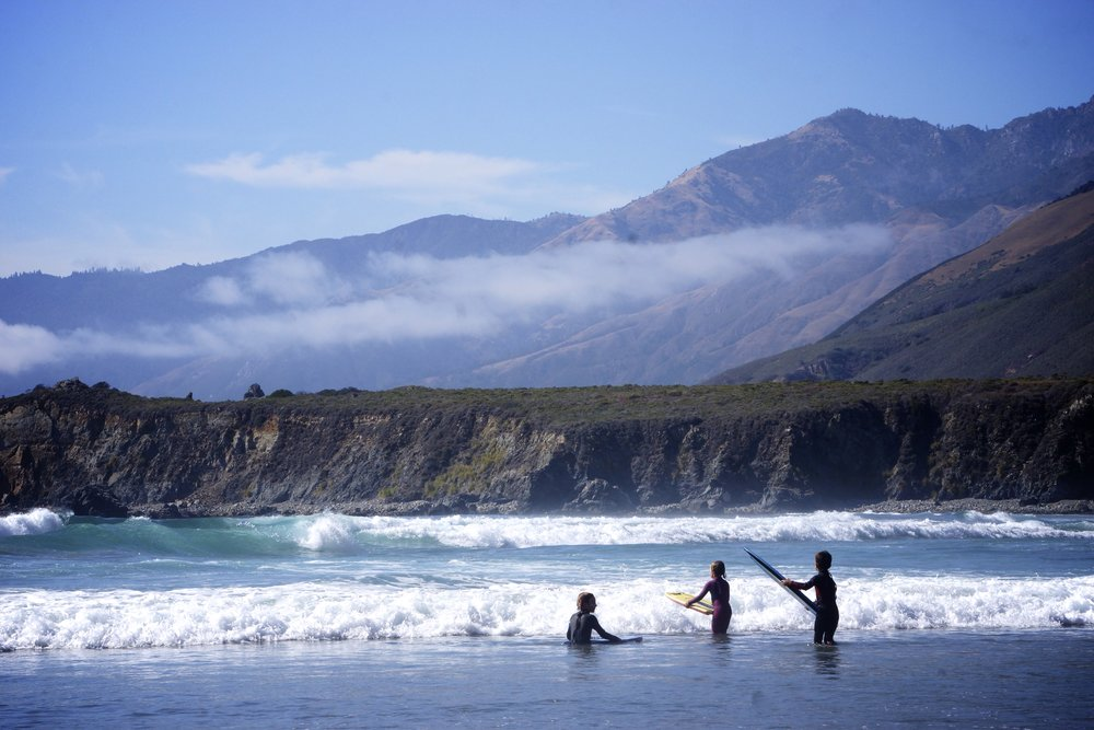 Children boogie board on the small waves of Sand Dollar Beach in Big Sur.