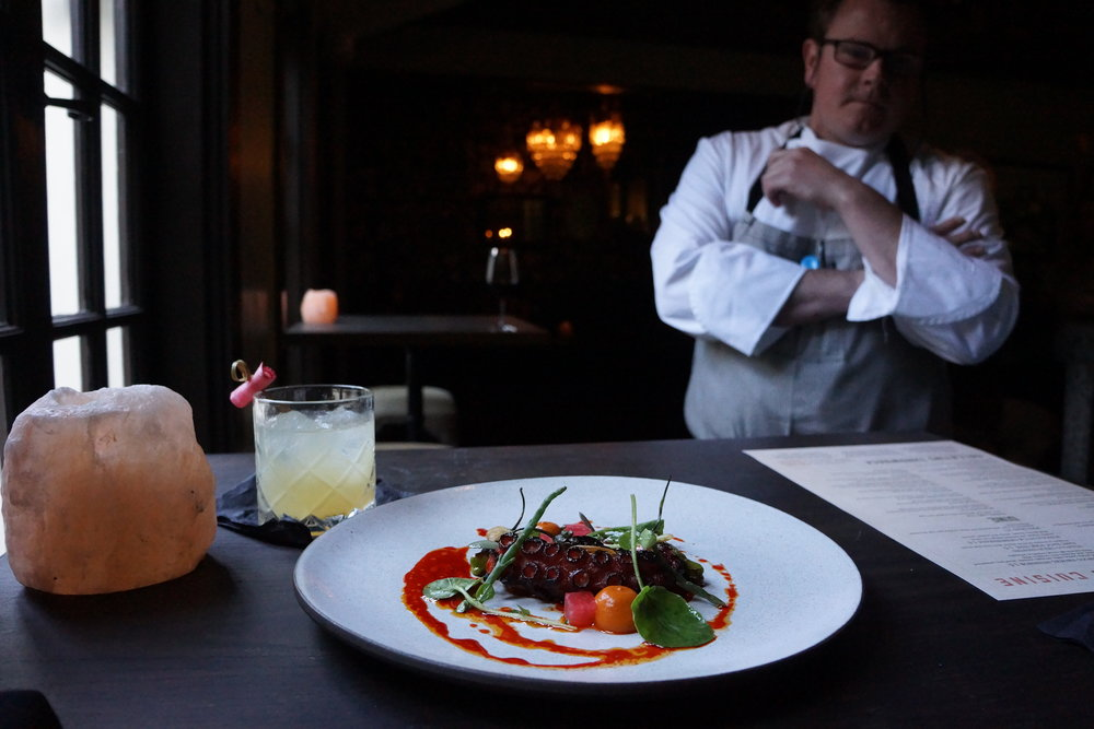 Executive chef of restaurant 1833, Jason Franey, surveys his wood fired octopus.