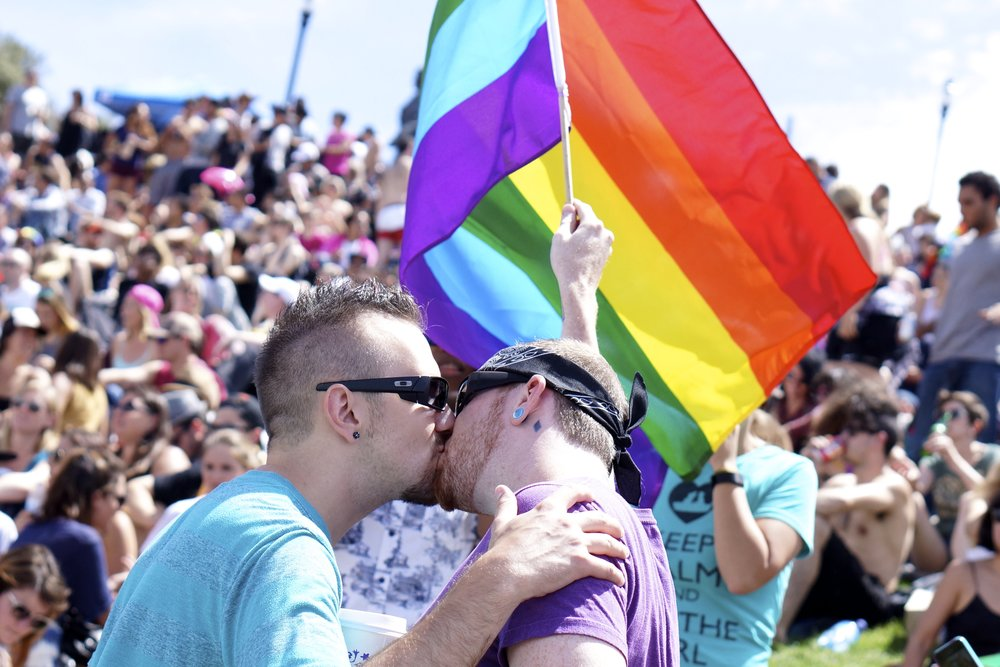 Two men kiss in front of a rainbow flag in San Francisco, celebrating the gay pride parade. The parade happened just days after the Supreme Court's June 26 decision to void Proposition 8, thereby allowing same-sex marriages to resume in the state.