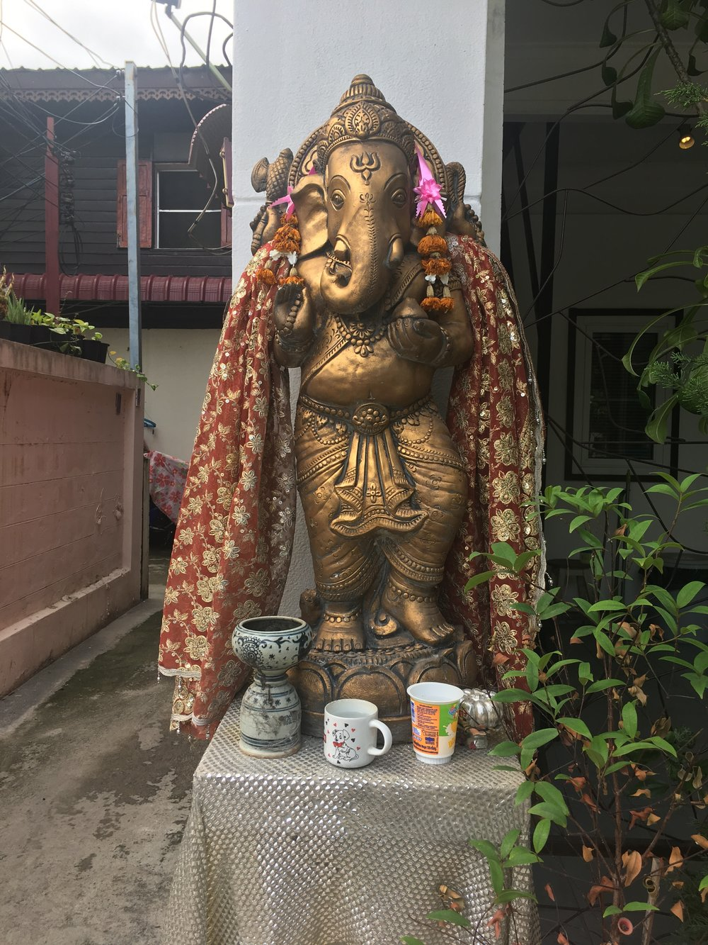 An altar in front of a small store. Ganesh must be thirsty!