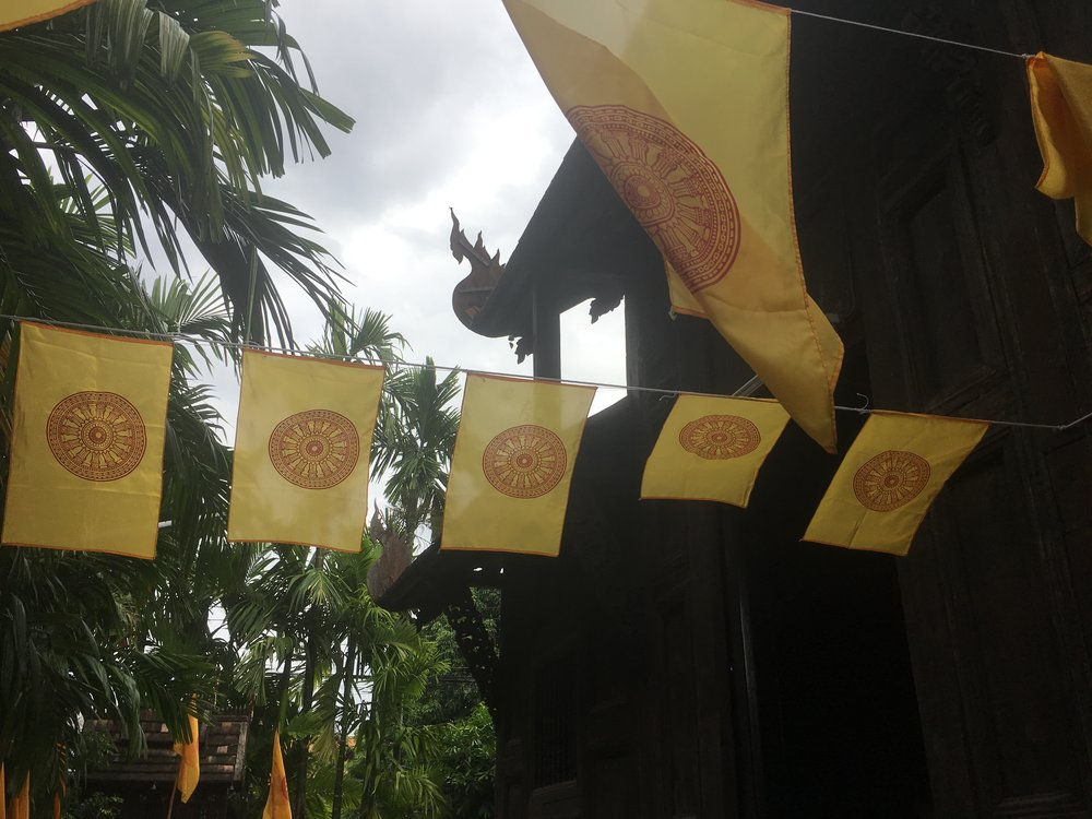 Buddhist prayer flags outside of the temple, representing the wheel of life or wheel of dharma. This wheel is specifically Tibetan but commonly found throughout Thailand. They are beautiful and simple! It would be cool to be the person who gets to silkscreen these for a living!