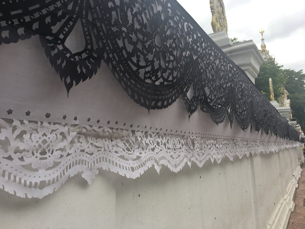 Hand-cut fabric banners outside of a temple. The black and white colors represent the late King who was very well-loved and passed away in October. The country is said to mourn him officially for one year and black and white decor around the city honors him.