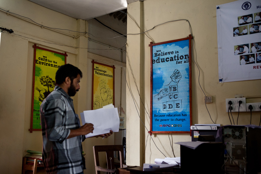 An office worker stands in front of welfare posters which advocates the companies underpinning of education.  The new generation are 93% literate, as opposed to 30% in the 1950's, and with children having aspirations for employment outside the industry, especially women.  The promotion and funding of education has created difficulties for the company who will face a severe labour shortage in the next 10 years, which in the future may only be solved by either using migrant workers or mechanisation.