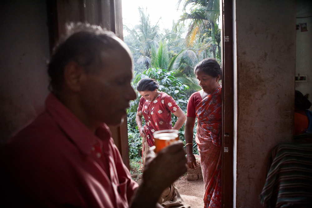 Bavani (central) changes from her day working clothes and enjoys a cup of tea with her extended family.  Many of the workers live in housing provided and tied to the company which are known as the 'line' as in, in-line housing.