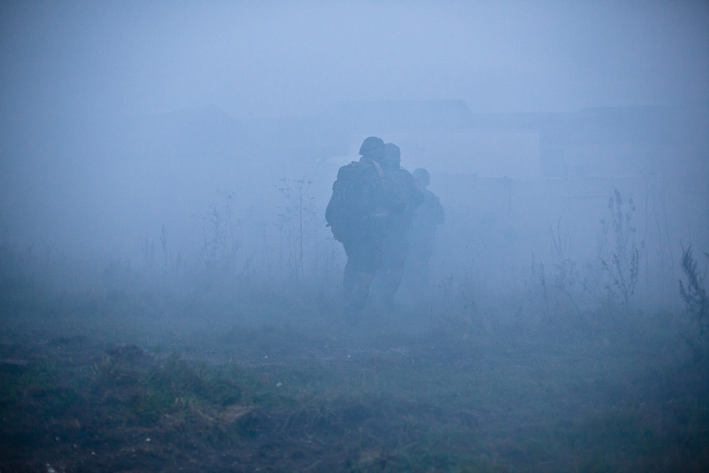 British and Dutch Royal Marines  advance after a smoke grenade is deployed to cover thier movements in a base assault during exercise Final Nail. This annual 10-day exercise is designed to encompass all the skills learned during their 15 months of training and is the last for the Royal Marines Young Officers before their passing out parade and deployment.