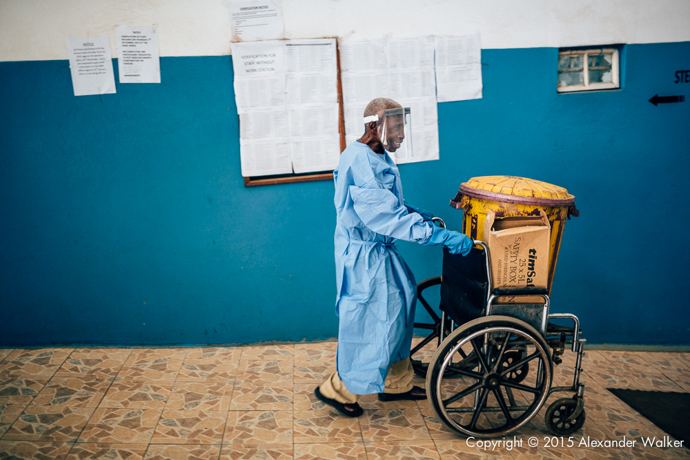 A man pushing a wheelchare with a bin of biologial wase at the OLA During Childrens Hospital, GAVI Alliance.  Comic Relief has funded GAVI since 2012 and awared funds in 2014 to purchace and deliver three lifesaving Vaccines to hundres of thousands of children in a selected number of African countries.  Immunisation is one of the most effective ways of preventing children from dying from diseses.  In africa alone, 600,000 children each year could be saved in vacccine programmes  were fully implemened.  Most countries have now introduced immunisation programmes in their national health plans, but almost a quater of african children are stil not being vaccinated adequately.