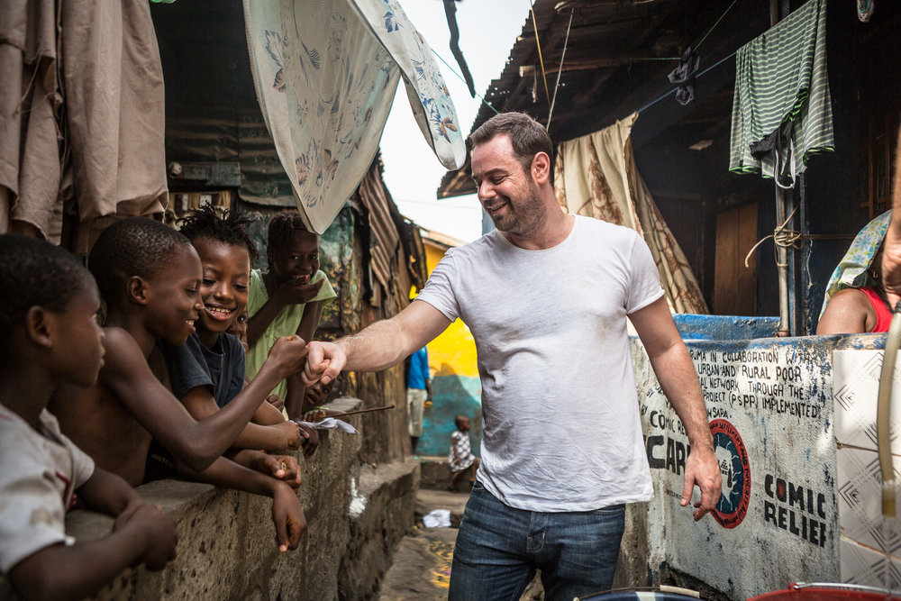 Danny Dyer visits a Comic Relief funded clean water tap in a  slum in Freetown.   The slum is supported by Y-Care international and local partner YMCA Sierra Leone.  Comic Relief Awarded these projects funds to provide 1800 unemployed young people with training, academic skills as well as metoring to assist them in finding jobs.  In addition awareness raising campaigns on hygine, with a bid to educating the population on the causes and spread of Ebola.
