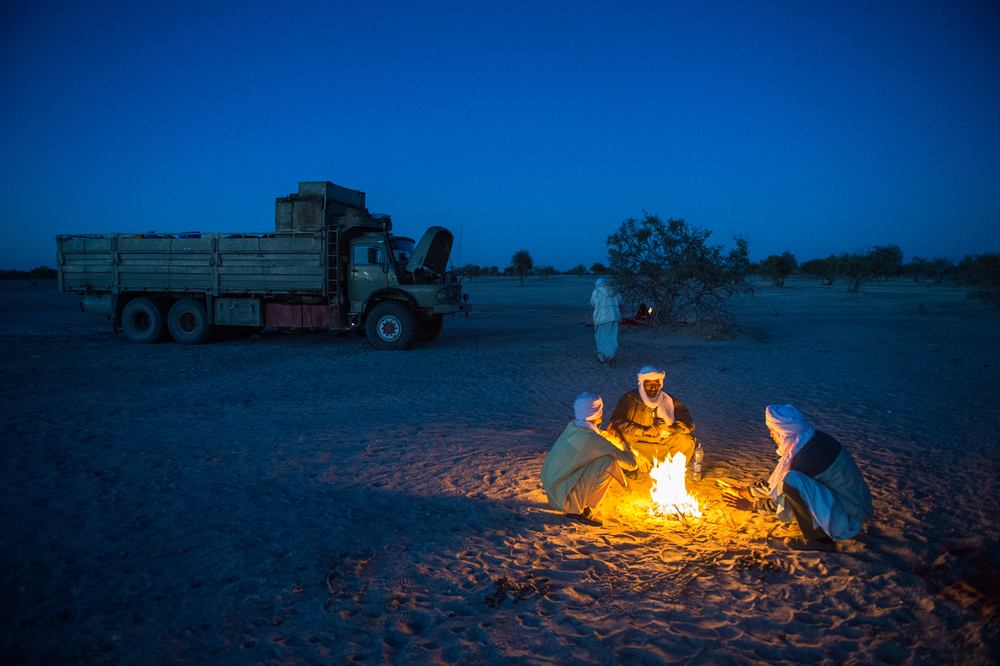 After a night in the desert and with nearly five more hours of travel to reach the village where they are opening a new school, Rivers and two teachers warm themselves by a fire before climbing back on a truck.