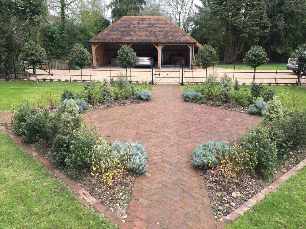 A new oak framed garage provides inspiration for the choice of materials - brick pavers and estate railings