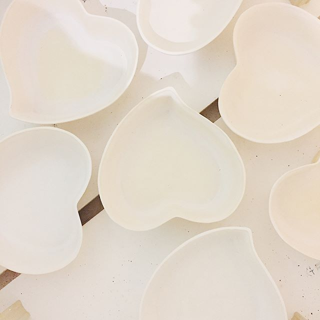 After the @breakfastcriminals ♥️heart bowls dry they get their first of 2️⃣firings in the kiln. My kiln is about 4 feet high x 3 feet wide and can hold a lot of product. The first firing, called a bisque fire, takes about 8 hours to get to a bit over 1,800 degrees Fahrenheit 🔥🙊🔥before clicking off and cooling down over the next 10 hours. All the dry clay pieces can touch each other so in these pictures you see other products (votive candle holders 🕯and mugs🍵and vases 🏺) stacked in the heart bowls. When they come out they're still hot but totally dry and ready for glazing 🎨At this stage they feel rough and almost brittle to the touch . . . . . #heartbowl #breakfastcriminals #harperkennedyceramics #porcelain #ceramics #handmade #brooklyn #gowanus #pottery #art #process #kiln #firing #bisque #skuttkilns @heartbowl