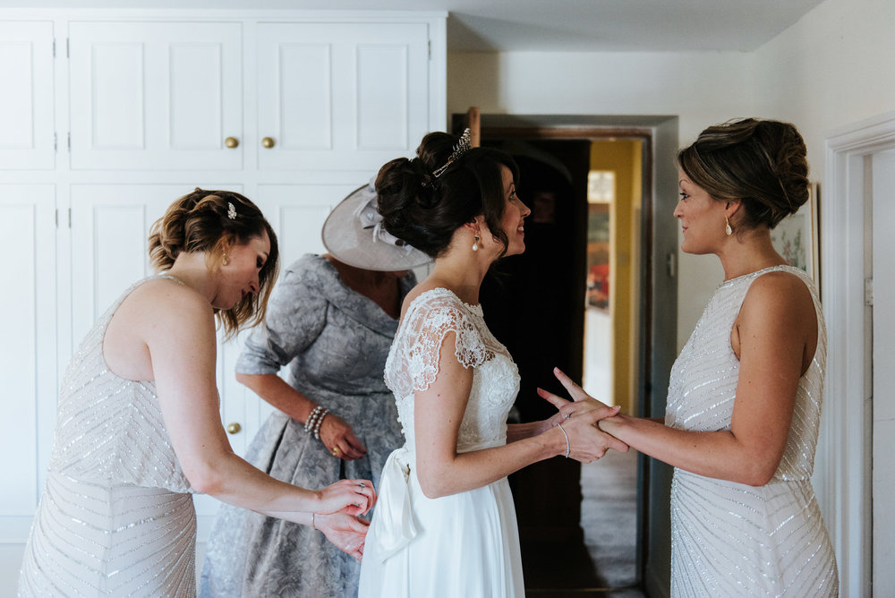 Bride very excited as bridesmaids help her put dress on inside h