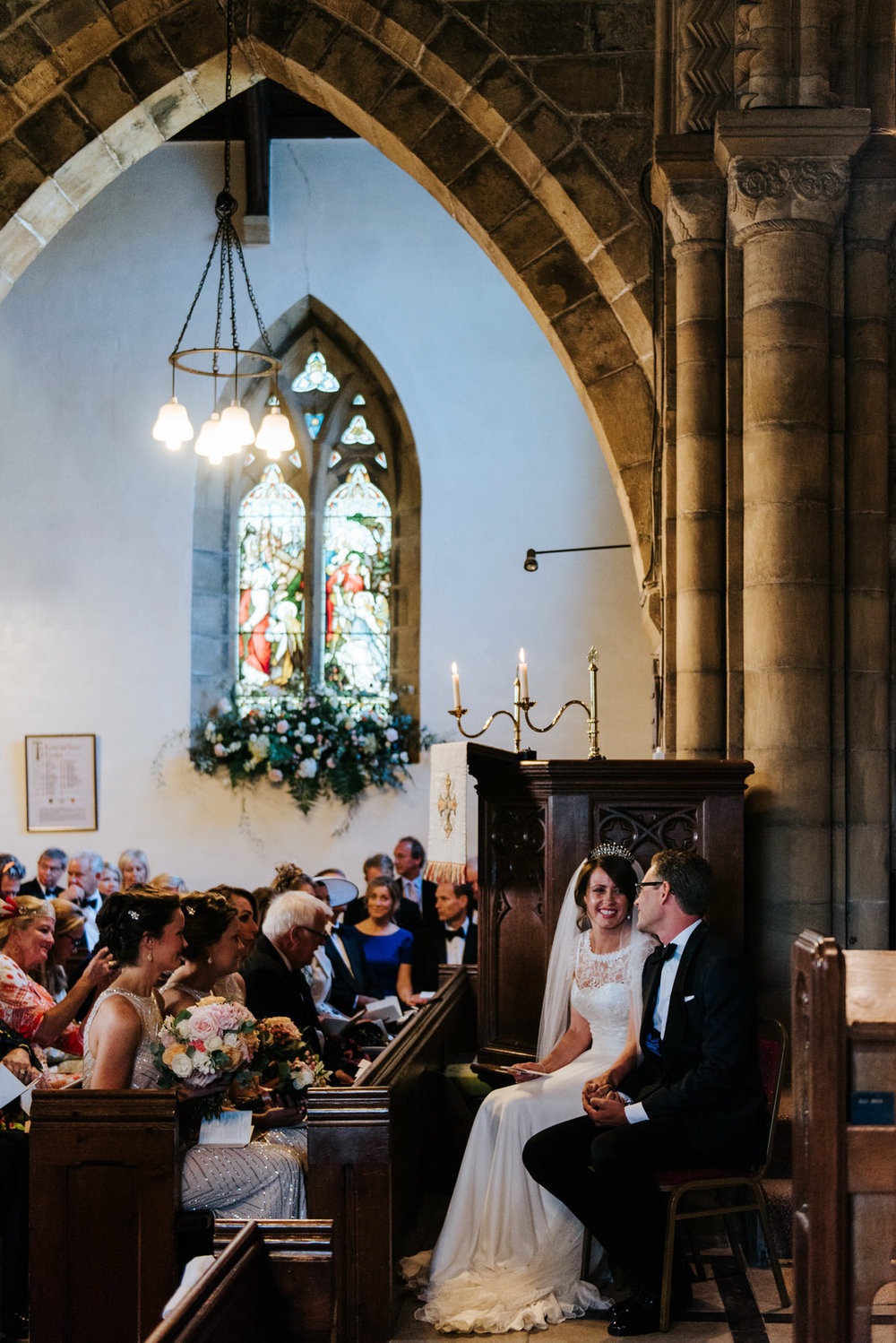 Bride and groom sat down smiling at each other in Church ceremon