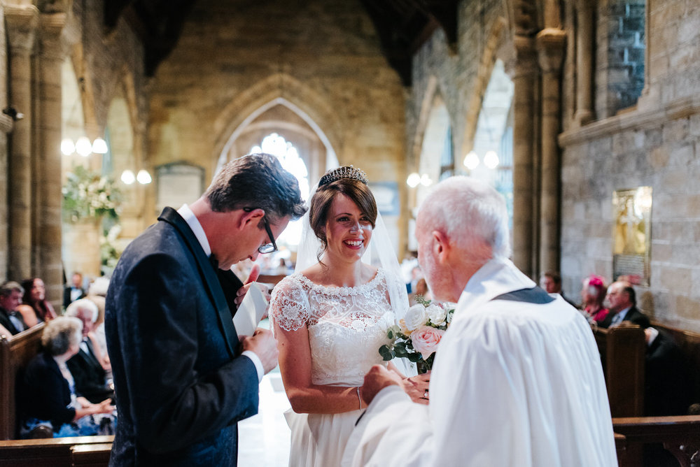 Vicar hands register to Groom towards end of Ceremony