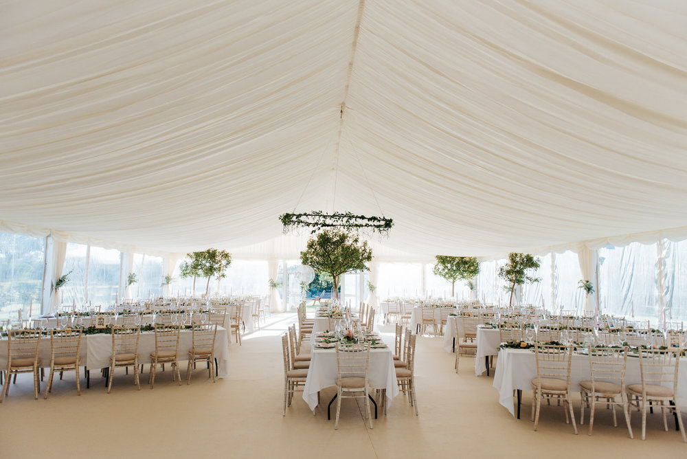 Beautiful white decor inside tree-lined garden marquee