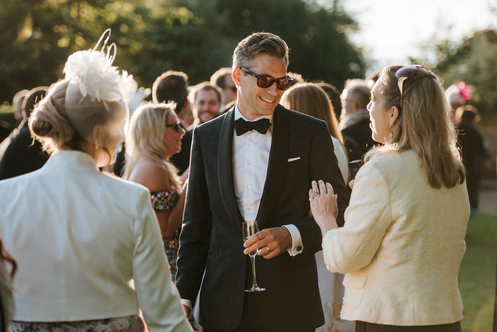 Groom drinking champagne and talking to guests outside the marqu