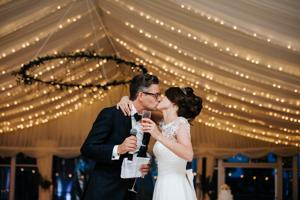 Bride and groom kiss romantically under Marquee fairy lights