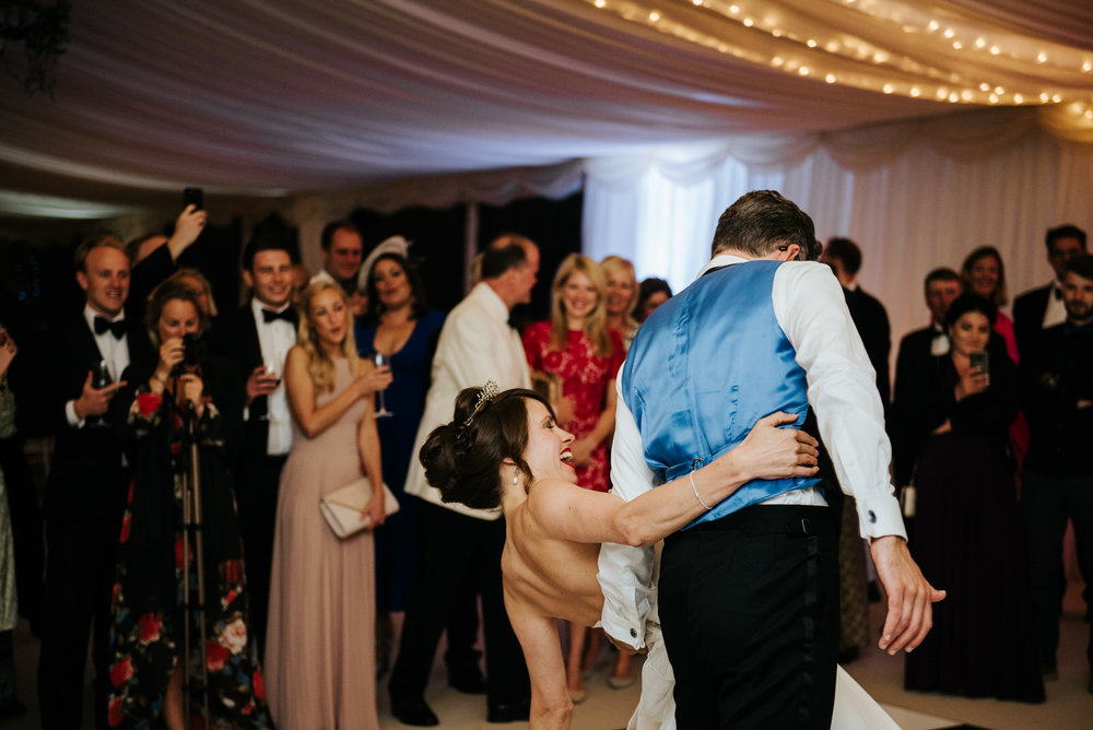 Groom dips bride as first dance inside marquee comes to an end