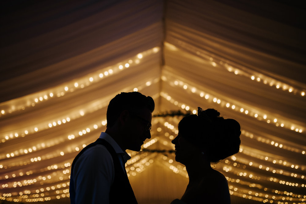 Silhouette portrait of bride and groom against marquee fairyligh