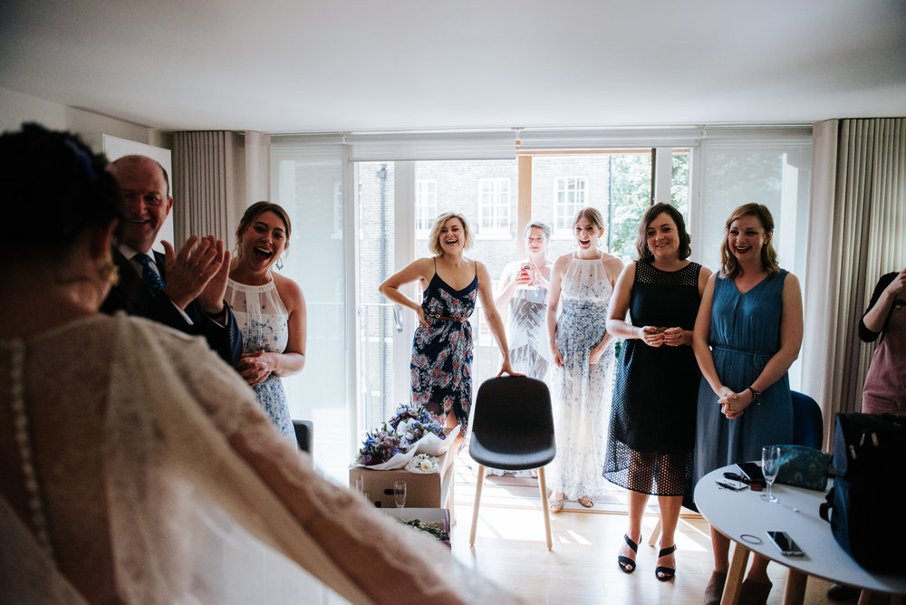 Bridesmaids react to seeing the bride in her dress for the first