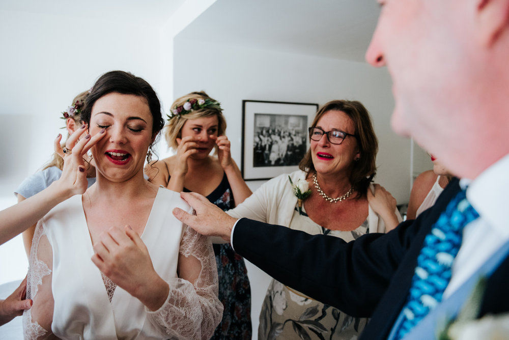 Bride cries as bridesmaids and parents form a circle around her