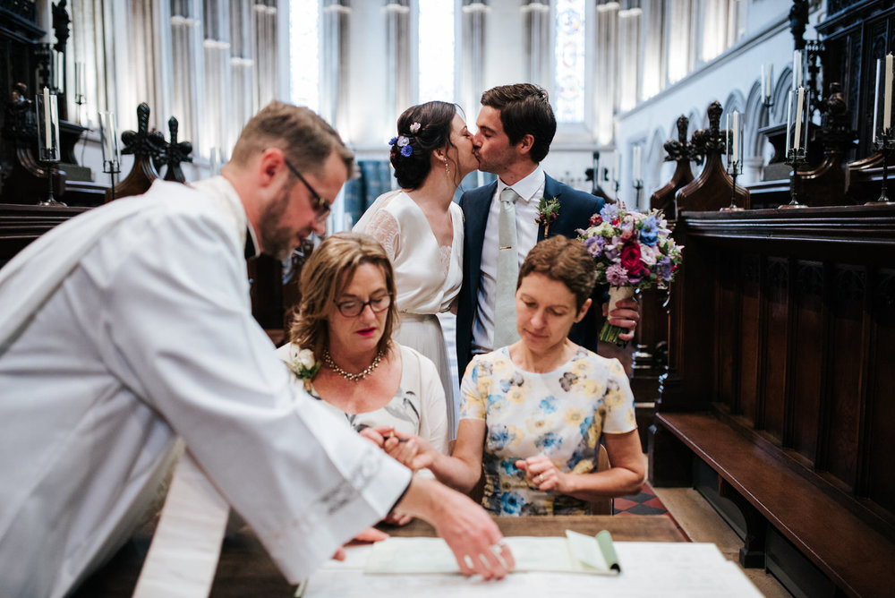 Bride and groom steal a kiss as witnesses sign register during w