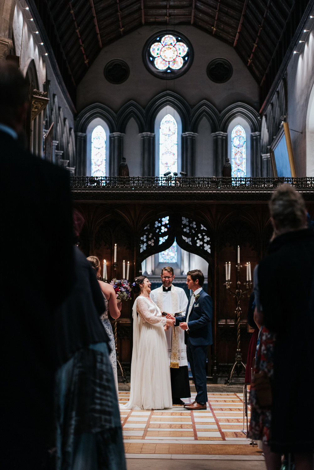 Bride and Groom hold hands and laugh out loud as vicar pronounce