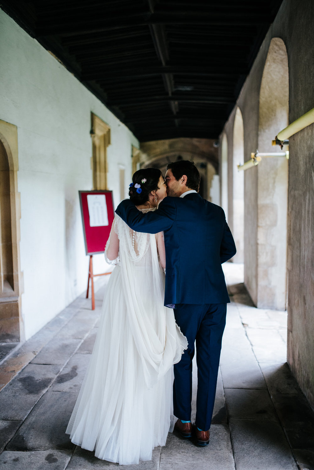 Bride and groom exit Jesus College Chapel and kiss as they are n