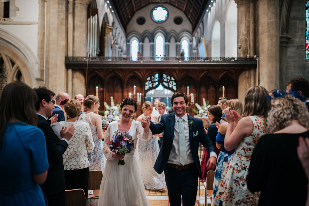 Bride and groom exit joyfully down the aisle at Jesus College Ca