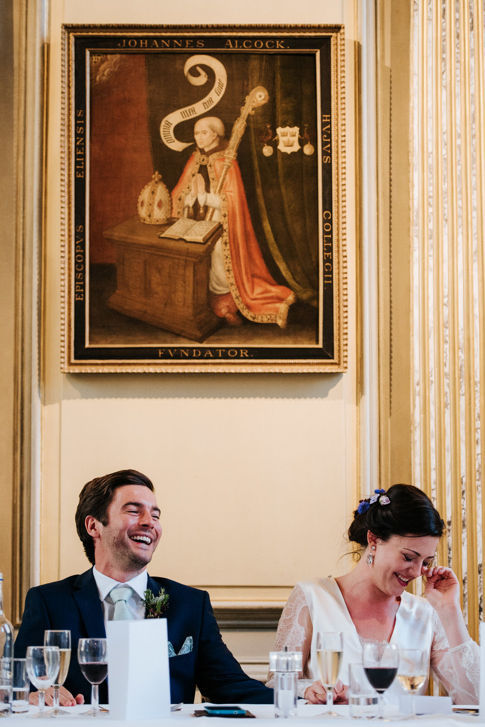 Bride and groom laugh out loud during speeches