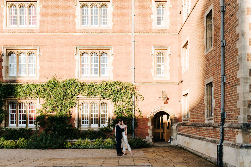 Bride and groom kiss and embrace in Jesus College Chapel Court