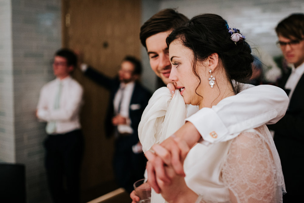 Bride reacts to speeches by tearing up as groom embraces her