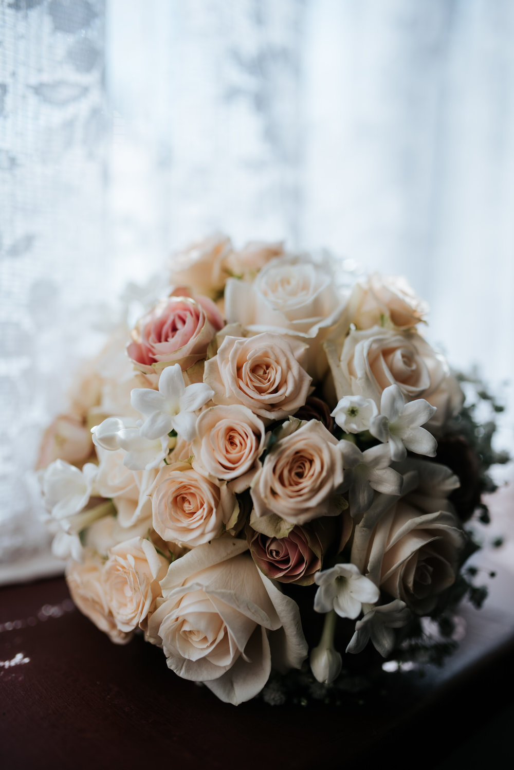 Beautiful white bridal bouquet in front of window