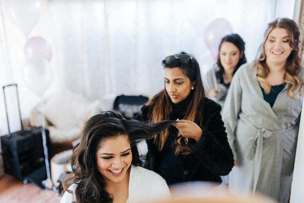 Bride getting her hair done as bridesmaids look from behind