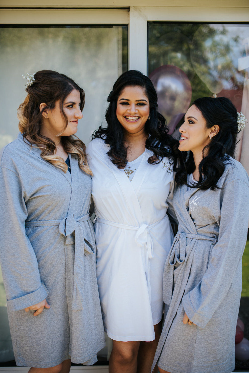 Bride and bridesmaids smile at each other as they are getting re