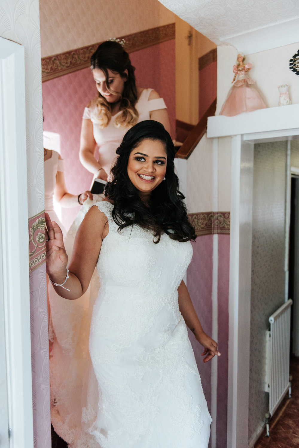 Bride walks down the stairs in her wedding dress in parent's hom