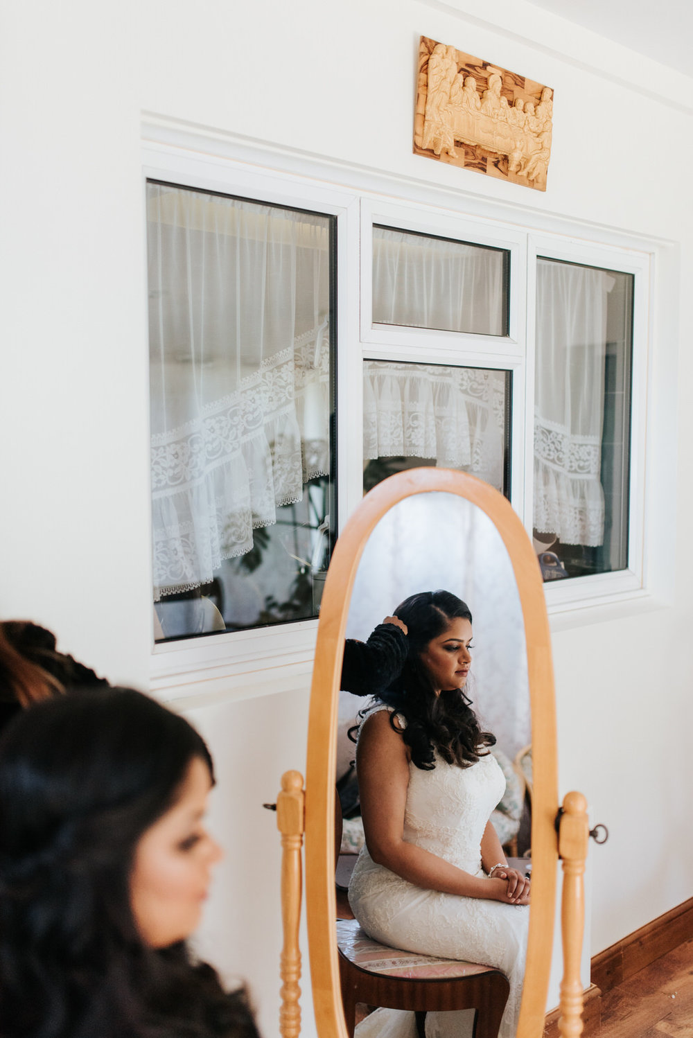 Bride has final adjustments done to hair before leaving for wedd