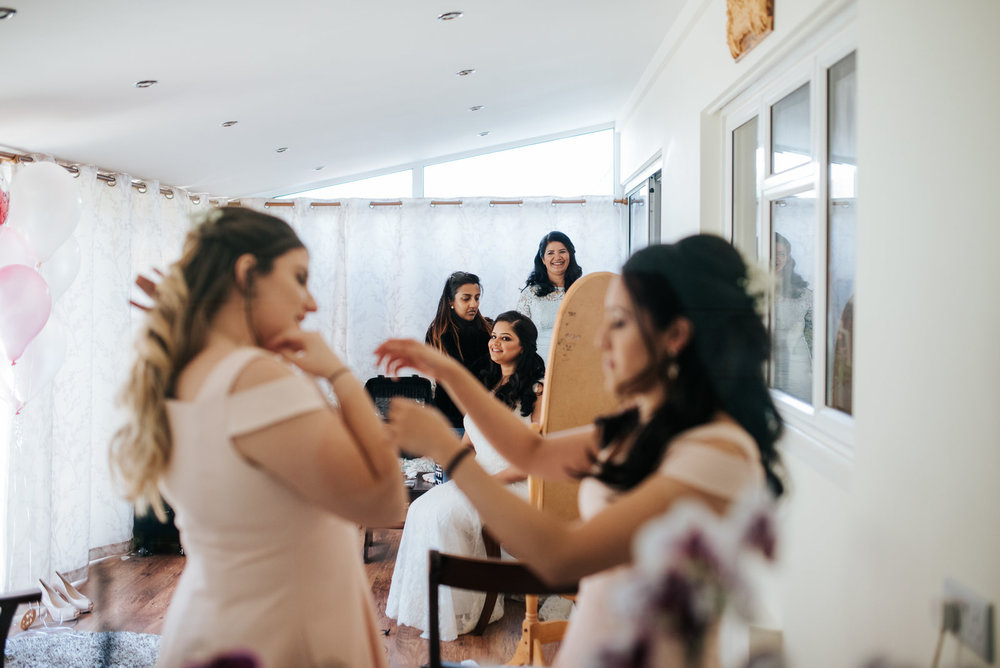 Bride looks at her bridesmaids as they finish getting ready
