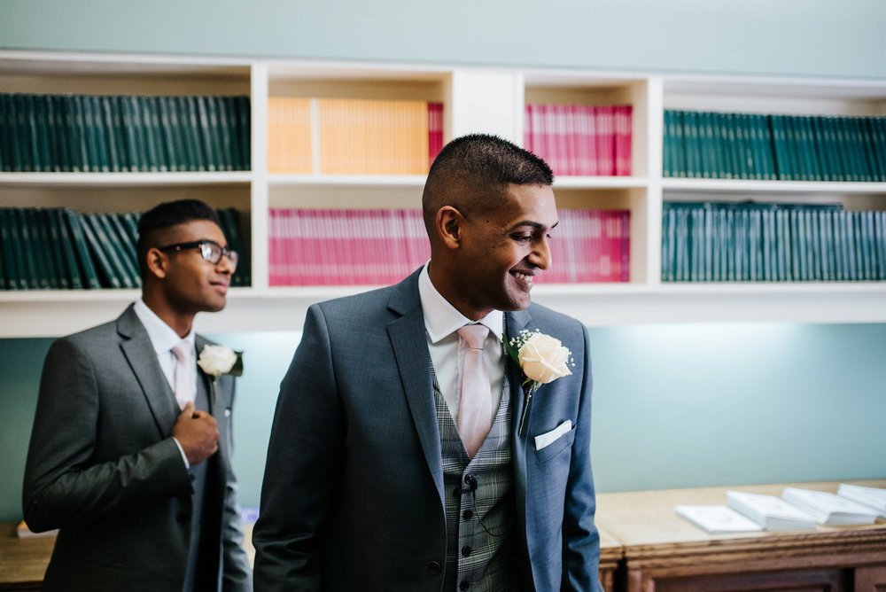 Groom greets guests alongside his brother in Woldingham School c