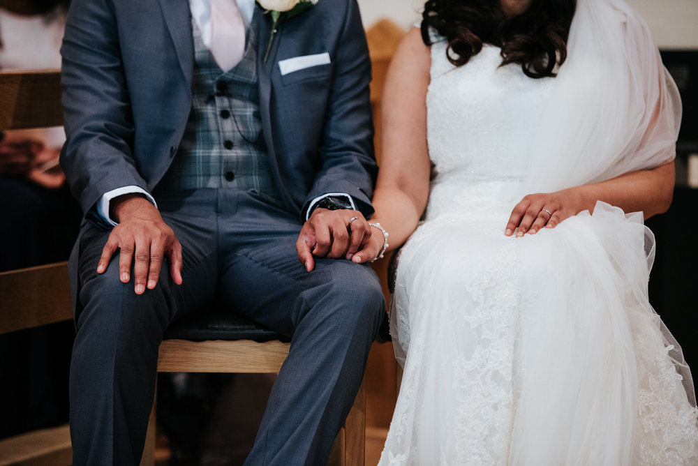 Bride and groom hold hands during wedding ceremony readings at W