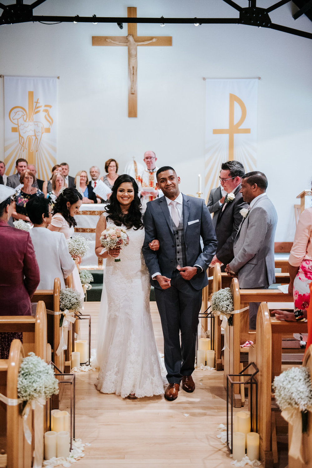 Bride and groom walk down the aisle at Woldingham School Chapel
