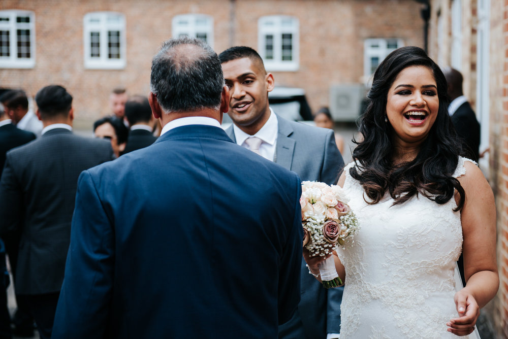 Bride smiles at guests outside chapel after wedding ceremony