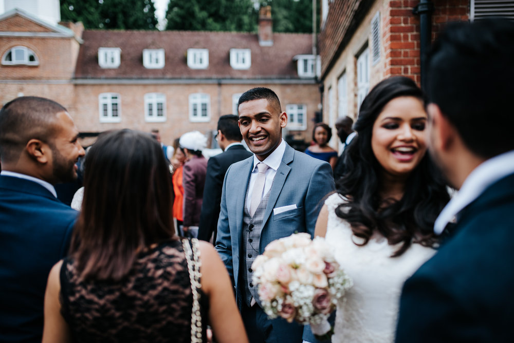 Groom welcomes and smiles at guests outside the chapel