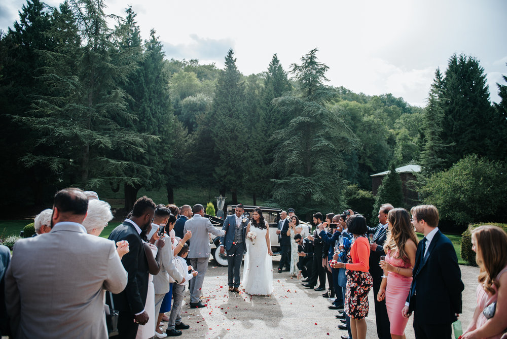 Wide shot of bride and groom walking down tunnel of guests as th