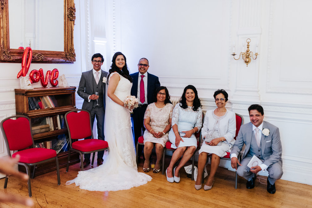 Bride and family members smile as they take a formal photo insid